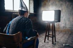 L'uomo di Afraided nel casco del di alluminio si siede in sedia Fotografia Stock