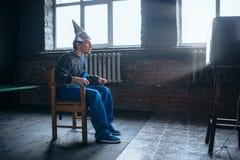 L'uomo di Afraided nel casco del di alluminio si siede in sedia Immagini Stock