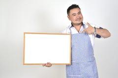 L'uomo di Asian del commerciante in grembiule bianco e blu a tenere vasto bianco in bianco per ha messo un certo testo o la formu fotografie stock libere da diritti