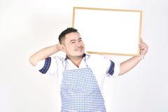 L'uomo di Asian del commerciante in grembiule bianco e blu a tenere vasto bianco in bianco per ha messo un certo testo o la formu fotografia stock