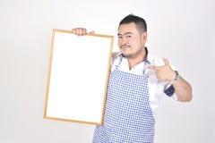 L'uomo di Asian del commerciante in grembiule bianco e blu a tenere vasto bianco in bianco per ha messo un certo testo o la formu immagini stock