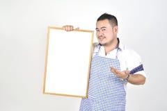 L'uomo di Asian del commerciante in grembiule bianco e blu a tenere vasto bianco in bianco per ha messo un certo testo o la formu immagine stock libera da diritti