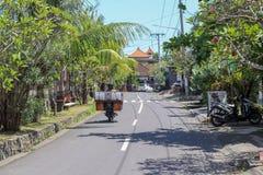 L'uomo di balinese con bagagli enormi sul motorino sul raod all'eco è fotografia stock