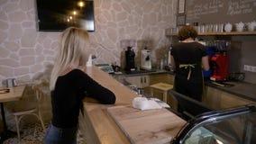 L'uomo di barista che pulisce il contatore quando un cliente femminile viene ed ordina un caffè a andare e paga con il bitcoin cr stock footage