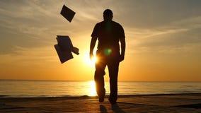 L'uomo di camminata getta un movimento lento vicino assente della siluetta della spiaggia del contratto - concetto di libertà stock footage