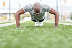 L'uomo di colore che di forma fisica esercitarsi spinge aumenta nel fondo urbano Fotografie Stock Libere da Diritti