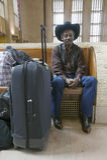 L'uomo di colore con le borse, il cappello da cowboy ed il cowboy calza il treno aspettante alla trentesima stazione della via, s Immagine Stock