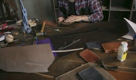 L'uomo di cuoio del lavoratore che si siedono dietro la tavola con gli strumenti e le tenute rivestono di pelle i portachiavi Fotografie Stock