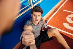 L'uomo di forma fisica con la bottiglia di acqua ha bisogno dell'aiuto allo stadio Fotografia Stock