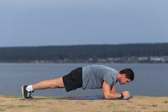 L'uomo di forma fisica di addestramento di Crossfit che fa l'esercizio del centro della plancia che risolve il suo centro del mid Fotografia Stock