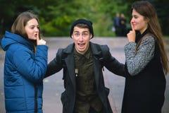 L'uomo di grido ha sollevato le mani e le ragazze provano a calmarla Fotografia Stock