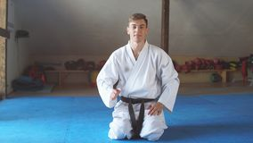 L'uomo di karatè in kimono si siede sulle ginocchia sul pavimento nella palestra di arti marziali archivi video