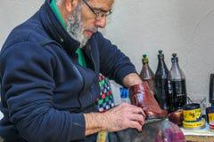 L'uomo di lucidatura delle scarpe sta lavorando Fotografia Stock
