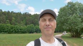 L'uomo di mezza età cammina nel parco, sparante in primo piano di moto video d archivio