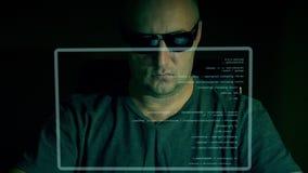 L'uomo di modo in vetri scuri si siede davanti allo schermo virtuale ed al codice di battitura a macchina sul computer Scritto di archivi video