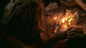 L'uomo di neandertaliano riscalda le sue mani dal primo falò nel suo scava stock footage
