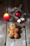 L'uomo di pan di zenzero di Natale con la cannella della candela stars la lampadina di natale del ramoscello del pino sul pavimen Immagini Stock Libere da Diritti
