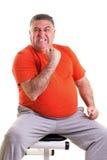 L'uomo di peso eccessivo che mostra la sua forza dopo avere fatto gli esercizi seted fotografie stock