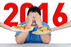 L'uomo di peso eccessivo con i numeri 2016 rifiuta gli alimenti industriali Fotografie Stock