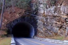 L'uomo di pietra ha fatto la fotografia della via e del tunnel di una strada attraverso una montagna Immagine Stock