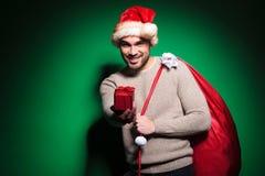 L'uomo di Santa sta offrendogli un piccolo contenitore di regalo Fotografia Stock Libera da Diritti
