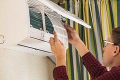 L'uomo di servizio è manutenzione del condizionatore d'aria Immagine Stock Libera da Diritti