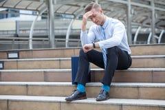 L'uomo di sforzo che si siede da solo sulla scala all'aperto Giovane gridare dell'uomo d'affari abbandonato ha perso nella depres immagini stock