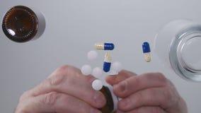L'uomo di sofferenza che prende le medicine seleziona le pillole a partire dalla superficie di vetro della Tabella immagini stock