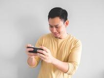 L'uomo di sorriso gioca il gioco mobile immagine stock