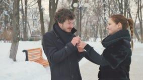 L'uomo di starnuto e la donna graziosa con lo spruzzo di naso nell'inverno parcheggiano stock footage
