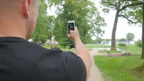 L'uomo di viaggiatore con zaino e sacco a pelo che viaggia nel parco e prende una foto in vacanza stock footage