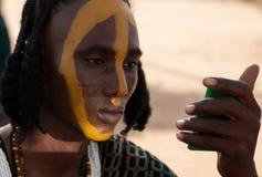 L'uomo di Wodaabe applica la pittura del fronte, Gerewol, Niger Fotografia Stock