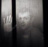 L'uomo dietro la finestra ritiene il timore Immagine Stock
