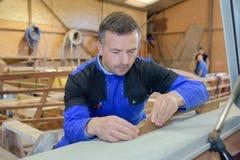 L'uomo dipinge l'oggetto di legno dall'officina fotografia stock