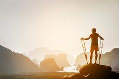 L'uomo disabile con le grucce su grande roccia sta come il vincitore fotografia stock