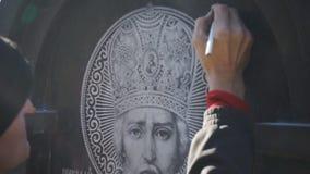 L'uomo disegna le marcature su una pietra stock footage