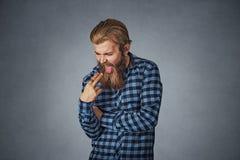 L'uomo disgustato con il dito in bocca dispiaciuto vuole gettare su immagini stock libere da diritti