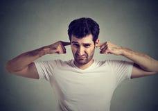 L'uomo dispiaciuto che tappa le orecchie con il ` t del doesn delle dita vuole ascoltare Fotografia Stock