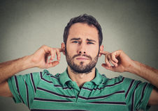 L'uomo dispiaciuto colpo in testa che tappa le orecchie con le dita non vuole ascoltare Fotografie Stock