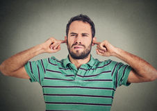 L'uomo dispiaciuto colpo in testa che tappa le orecchie con le dita non vuole ascoltare Fotografia Stock