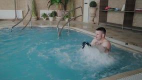 L'uomo divertente allegro bagna nella Jacuzzi dello stagno e lava il suo mette video d archivio