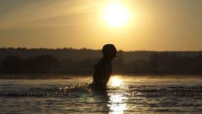 L'uomo divertente batte l'acqua del lago per intrattenere al tramonto nel slo-Mo archivi video
