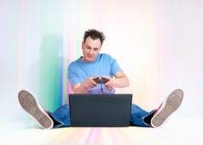 L'uomo divertente con la leva di comando si siede sul pavimento multicolore davanti ad un computer portatile Giochi del Gamer Immagini Stock Libere da Diritti