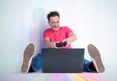 L'uomo divertente con la leva di comando si siede sul pavimento multicolore davanti ad un computer portatile Giochi del Gamer Immagine Stock Libera da Diritti