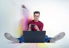 L'uomo divertente con la leva di comando si siede sul pavimento multicolore davanti ad un computer portatile Giochi del Gamer Immagine Stock