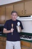 L'uomo divertente del celibe che cucina il pranzo mangia dal barattolo di latta Immagine Stock