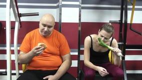 L'uomo divertente grasso sta mangiando il humburger in una palestra, vicino lui giovani belle ragazze con il porro stock footage