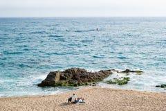 L'uomo e il wooman adulti hanno un sunbath alla spiaggia Fotografia Stock