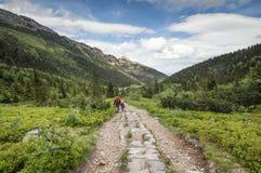 L'uomo e la bambina vanno sulla traccia di montagna fra catena montuosa due Fotografia Stock Libera da Diritti