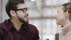 L'uomo e la donna adulti stanno tenendo i presente di ciascuno e stanno baciando dalla tavola archivi video
